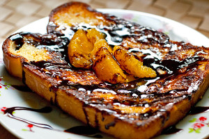 Orange French toast drizzled with honey and chocolate sauce